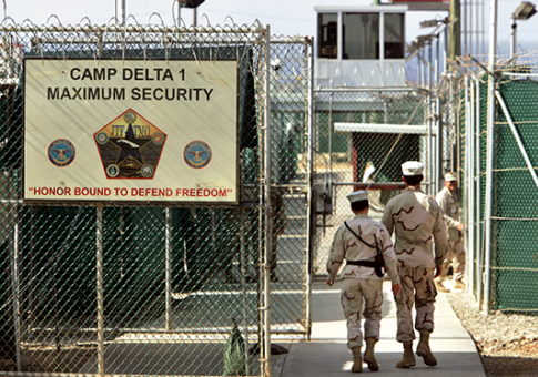 U.S. military guards walk within Camp Delta at Guantanamo Bay in 2006 / AP