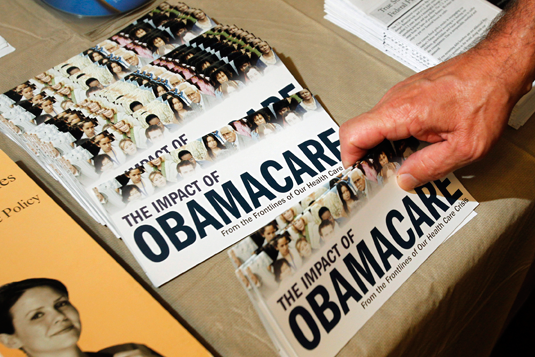 "A Tea Party member reaches for a pamphlet titled ""The Impact of Obamacare"", at a rally in Littleton, N.H., in this Oct. 27, 2012 photo. REUTERS/Jessica Rinaldi//Files"