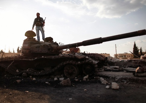 A Free Syrian army fighter stands on a damaged military tank / AP