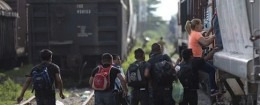 Immigrants run to jump on a train during their journey toward the U.S.-Mexico border / AP