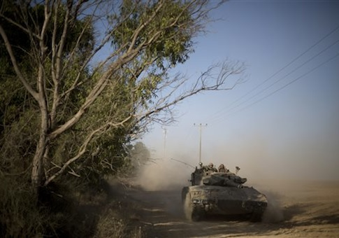 Israeli soldiers drive a tank to a position near the Israel Gaza border, Thursday, July 10