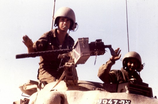 Israeli troops wave from the turret of their tank, somewhere in the Sinai Desert during the Yom Kippur War Oct. 12, 1973. / AP