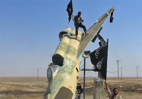 This undated file image posted by the Raqqa Media Center, in Islamic State group-held territory, on Wednesday, Aug. 27, 2014, which has been verified and is consistent with other AP reporting, fighters of the Islamic State wave the group's flag from a damaged display of a government fighter jet following the battle for the Tabqa air base, in Raqqa, Syria