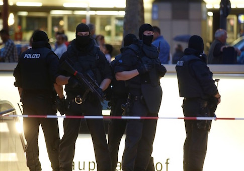 Special force police officers stand guard at entrance of main train station following shooting rampage at shopping mall in Munich