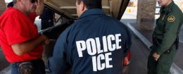 Special agents from Immigration and Customs Enforcement question a man while his vehicle is searched