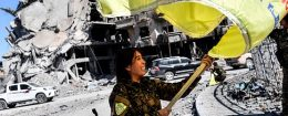"Rojda Felat, a Syrian Democratic Forces (SDF) commander, waves her group's flag at the iconic Al-Naim square in Raqa on October 17, 2017. US-backed forces said they had taken full control of Raqa from the Islamic State group, defeating the last jihadist holdouts in the de facto Syrian capital of their now-shattered ""caliphate"". / Getty Images"
