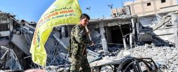 A member of the Syrian Democratic Forces holds up their flag at the iconic Al-Naim square in Raqqa