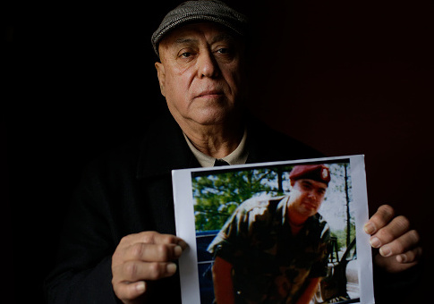 Miguel Perez poses as he holds a photo of his son Miguel Perez Jr. / Getty Images