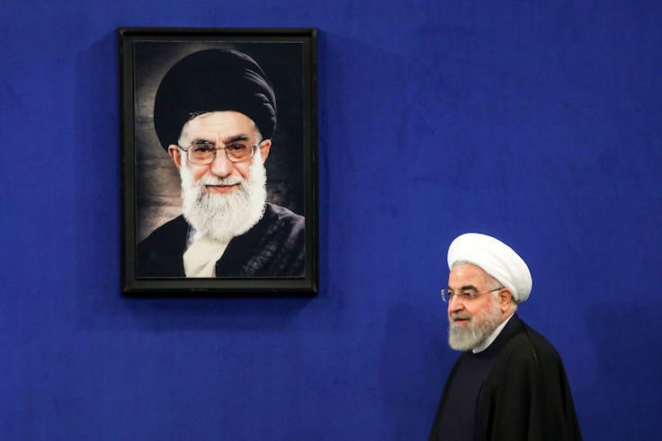 Iranian President Hassan Rouhani walks past a portrait of Supreme Leader Ayatollah Ali Khamenei
